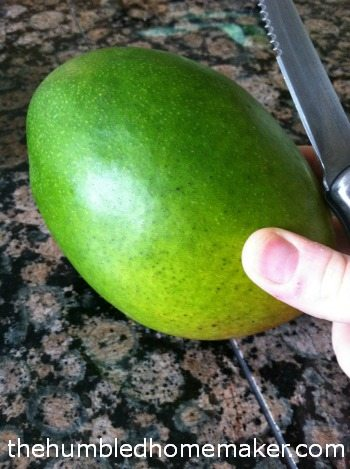 cutting into a mango