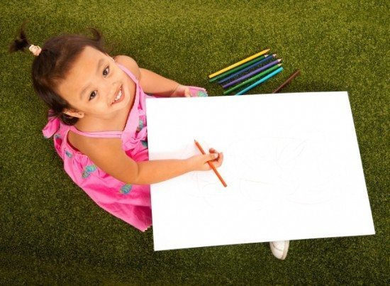 Child Sitting On The Grass Drawing A Picture With Multi Colorored Pencils