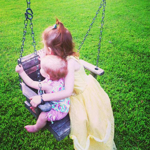 Holding baby sister on swing