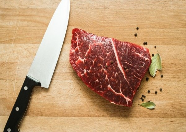 Fresh raw beef on wooden cutting board with  pepper