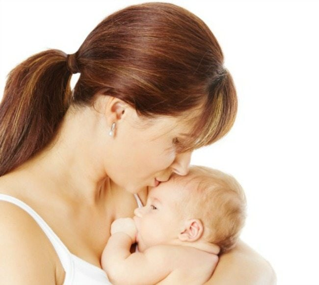 Mother kissing newborn baby holding in hand over white background