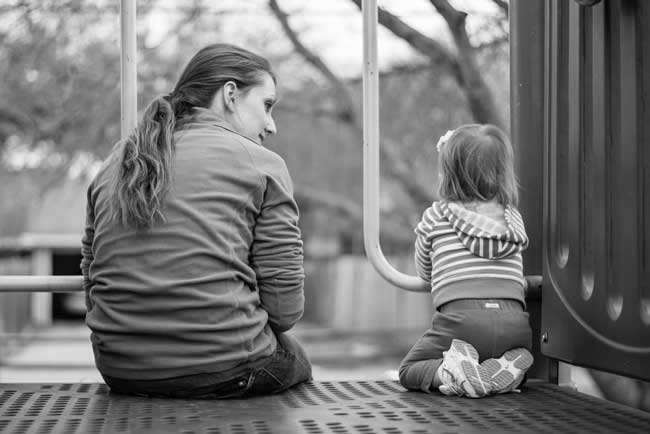 Mother and child sitting together at the playground. Getting down at eye level is just one ways to help time stand still and promote moments of connection with your kids.