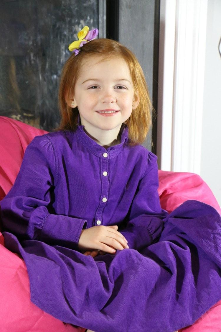 In her purple Schoola dress