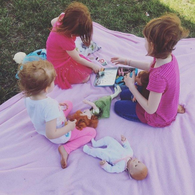 girls having a picnic with their dolls